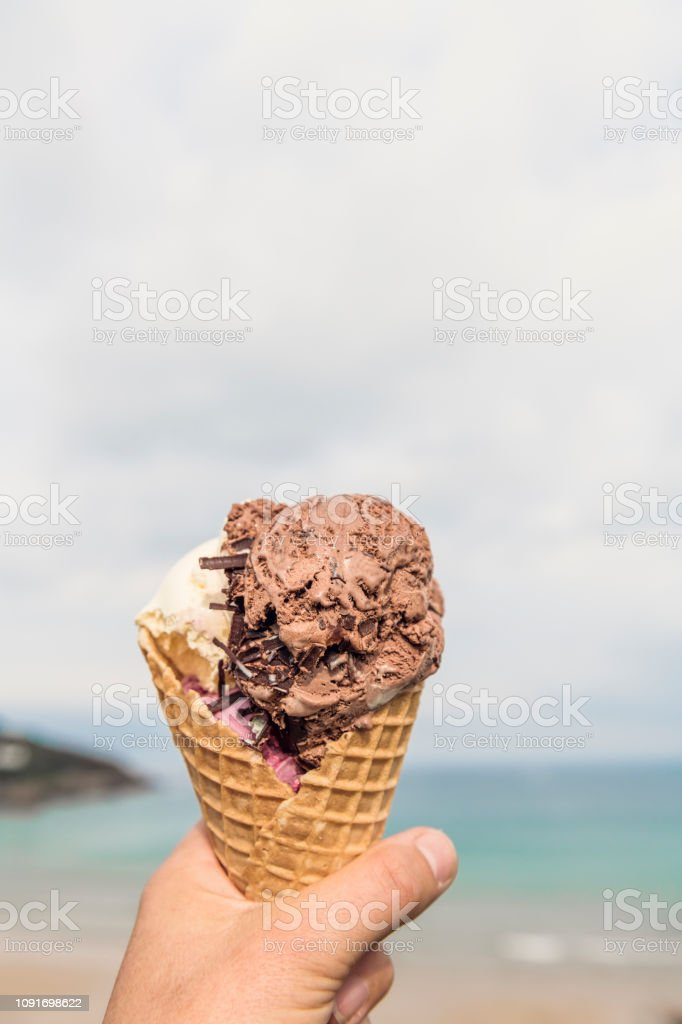 POV of a hand holding a large 3 scoop ice-cream cone at the beach, Newquay, Cornwall. stock photo