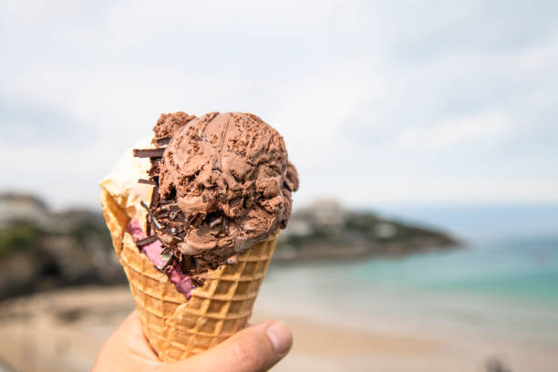 pov of a hand holding a large 3 scoop ice-cream cone at the beach, newquay, cornwall. - ice cream cone stock pictures, royalty-free photos & images