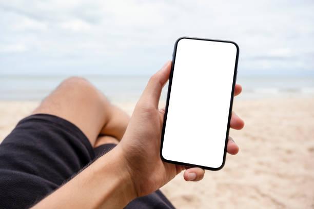 eine Hand hält und zeigt schwarzes Handy mit leerem Desktop-Bildschirm, während auf dem Strandstuhl sitzen – Foto