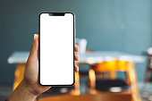 istock a hand holding and showing black mobile phone with blank screen in cafe 1190965421