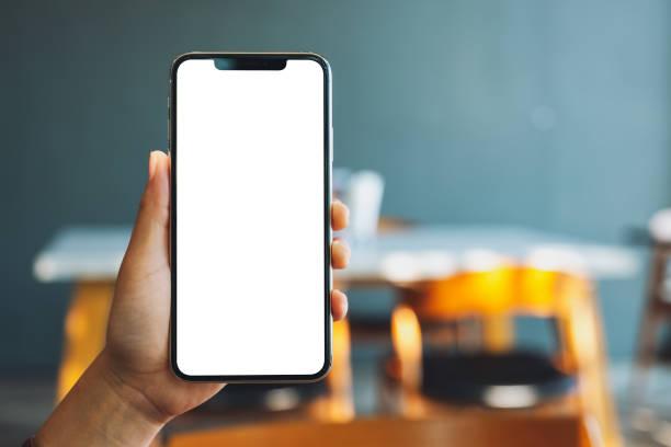 eine Hand hält und zeigt schwarzes Handy mit leerem Bildschirm im Café – Foto