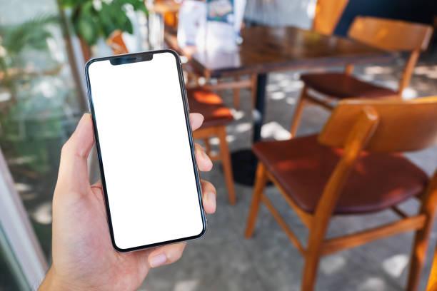 eine Hand hält und zeigt schwarzes Handy mit leerem weißen Bildschirm im Café – Foto
