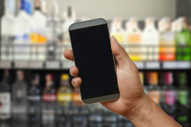 a hand holding blank screen smartphone on wine liquor bottle on shelf - hand holding phone zdjęcia i obrazy z banku zdjęć