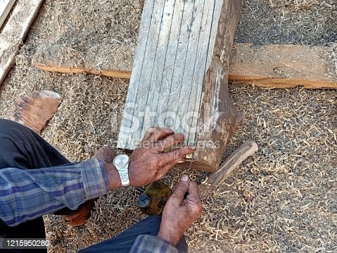 a hands of carpenter marking on wooden texture before sawing and split the wood to small sheet
