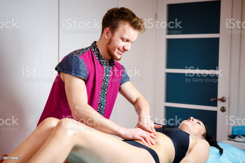 young man massage therapist,therapist doing massage girl on muscles...