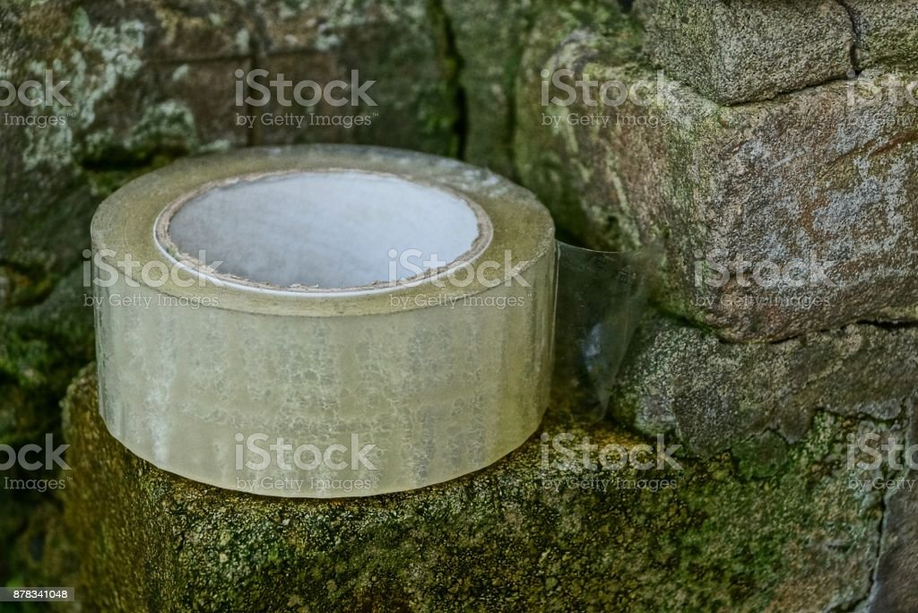 a hank of transparent adhesive tape lies on the bricks of the wall stock photo