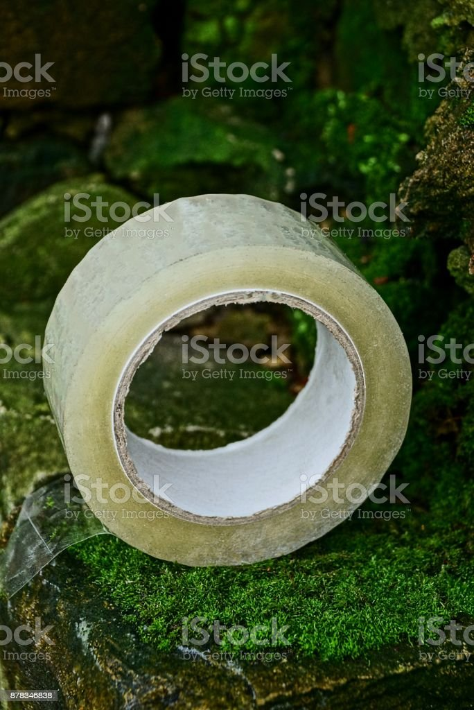 a hank of transparent scotch lies on old stones covered with moss stock photo