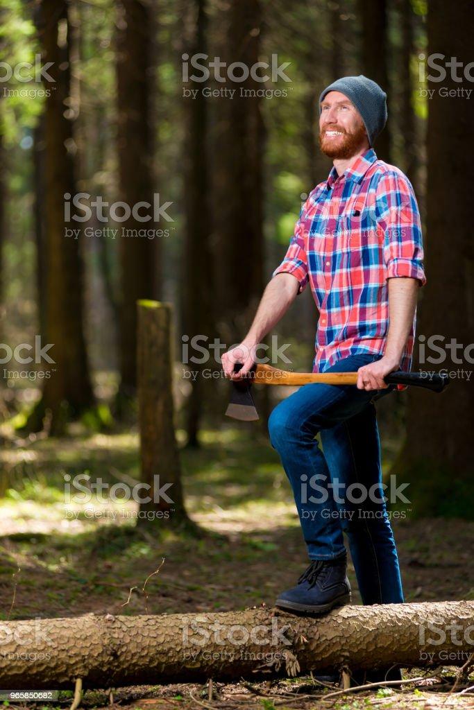 een gelukkig boswachter met een bijl in de buurt van de met dumping boom in het bos glimlacht - Royalty-free Alleen mannen Stockfoto
