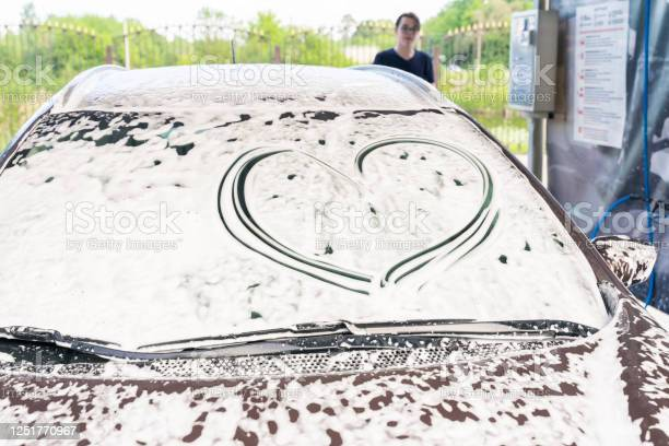 Photo of a heart is drawn on the car glass in foam at a car wash. the man in the background. symbol of respect for the car of the client