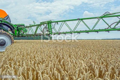 a high-clearance, modern sprayer over the wheat field.