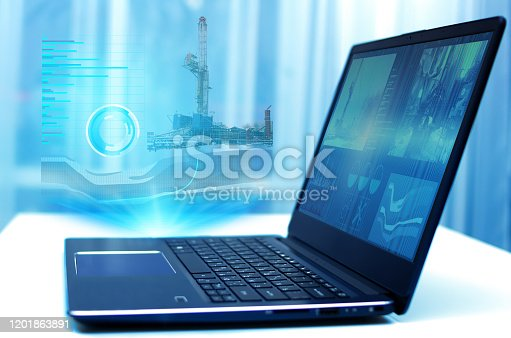 istock a hologram on a laptop, drilling a well to monitor and analyze geology in oil and gas production. Modern technology and artificial intelligence 1201863891