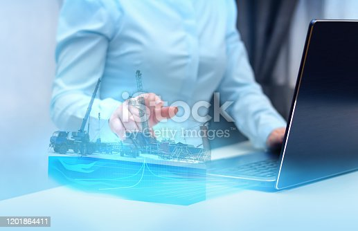 istock a hologram on a laptop, drilling a well to monitor and analyze geology in oil and gas production. Modern technology and artificial intelligence 1201864411