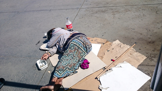 Istanbul, Turkey - April 21, 2016: a poor woman lying down on cement beton ground and begging for helping panhandler asker aid human relations street city life concepts