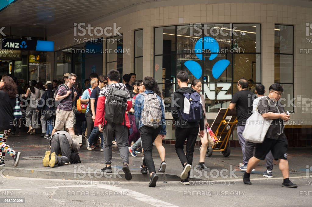 a homeless man is kneeing on corner of footpath in busy city front of ANZ bank, Sydney Australia 25-11-17 stock photo
