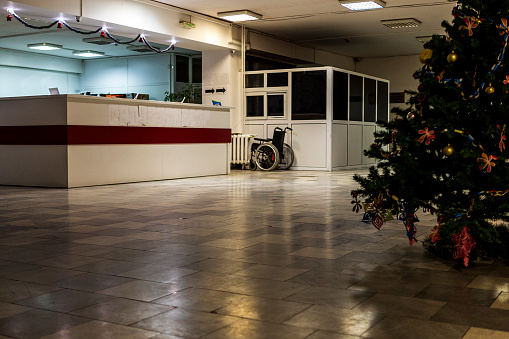 istock a hospital interior with a decorated Christmas tree and a wheelchair in the background. 1084928832