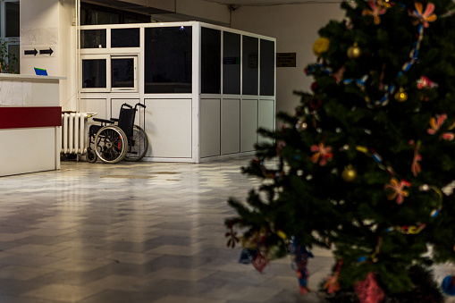 istock a hospital interior with a decorated Christmas tree and a wheelchair in the background. 1084928896