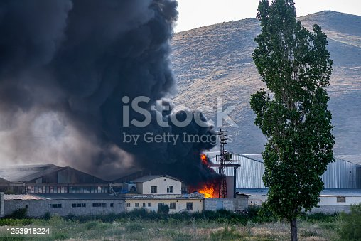 a huge factory fire. black fumes and flames