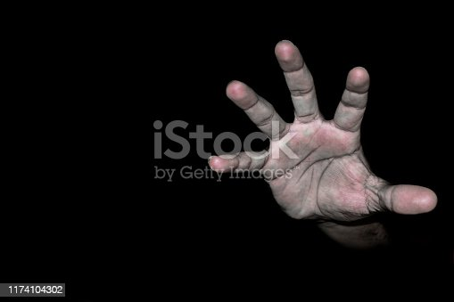 a human hand apearing from the darkness as ghost hand and darkness in the background