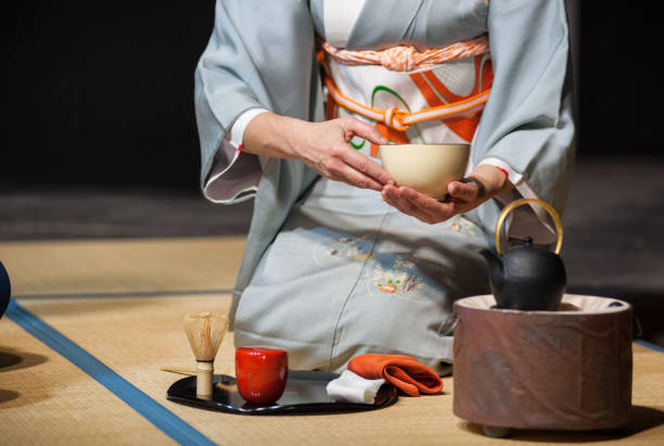 """a japanese woman shows the tea ceremony during a public demonstration Florence, Italy - 2018, November 24: Japanese woman with light blue kimono holding a teacup, during the traditional tea ceremony, at the """"Japan Festival 2018"""" free public event. geisha stock pictures, royalty-free photos & images"""