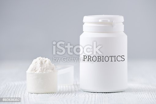 a white jar and spoon with probiotic powder on gray background