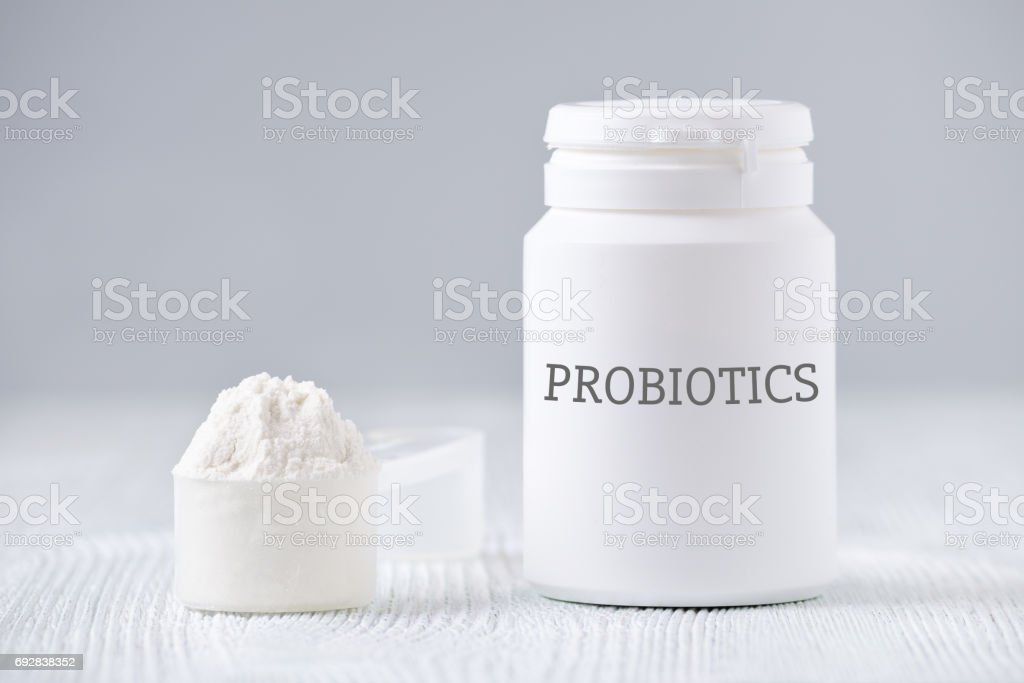 a jar and spoon with probiotic powder on gray stock photo