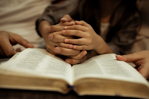 a kid reading the holy bible with guide by parents