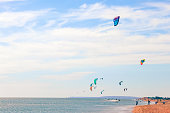 a kitesurfer surfing on the smooth azure water. recreational sport. A Man Rides A Kiteboarding In The Sea Water. extreme sport. High quality photo