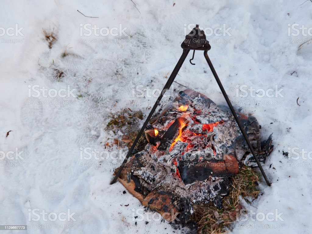 a large campfire with a tripod above it and a hook for cooking on a...