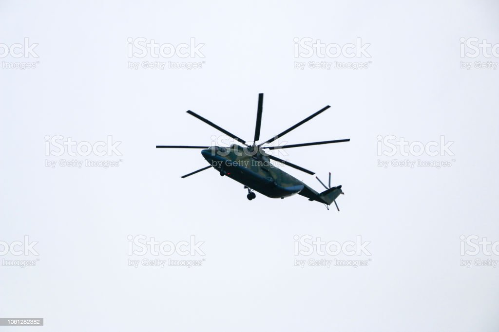 a large military helicopter hovers in the sky. A camouflaged helicopter flies at high speed. stock photo