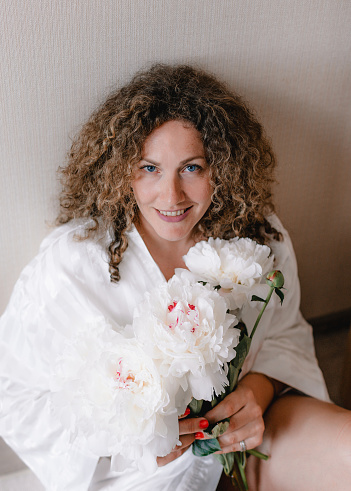 a large portrait of a woman with curly hair holding a bouquet of white peonies in her hand.