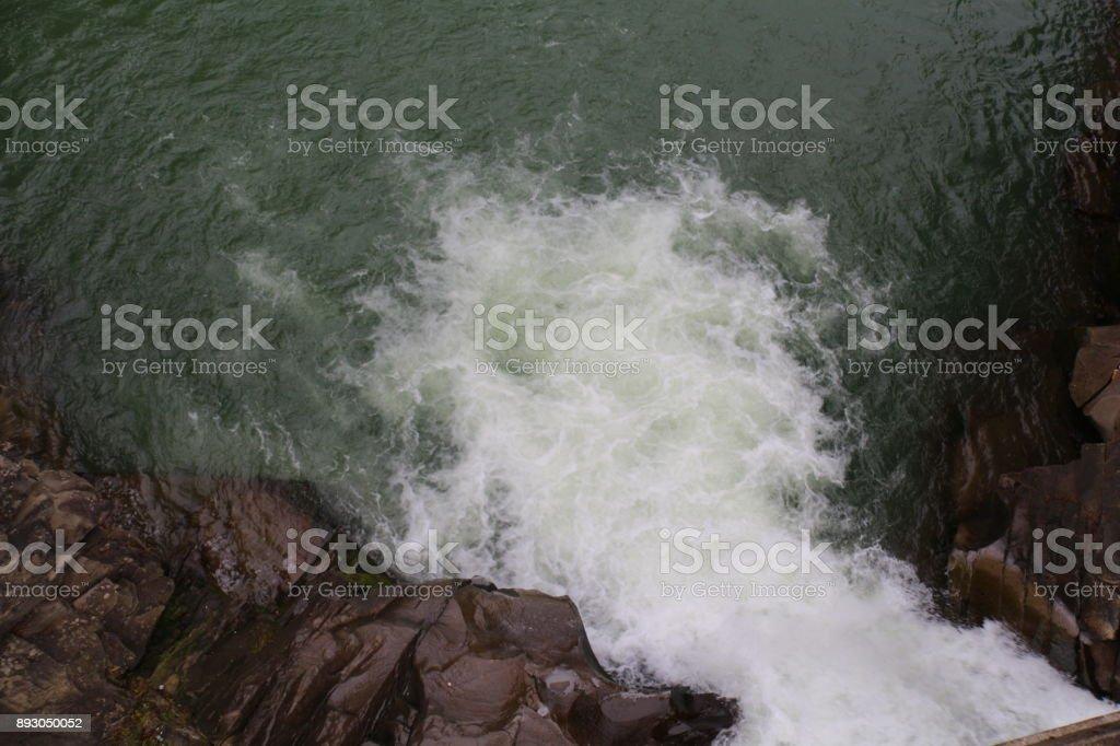 una gran roca en medio de un río de montaña - foto de stock