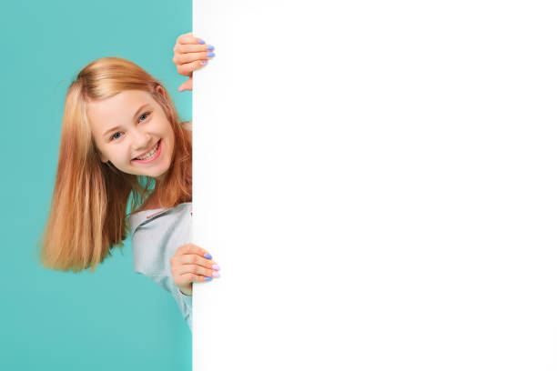 a laughing girl standing against a turquoise background holds an empty white Board in her hand and looks out from behind it stock photo