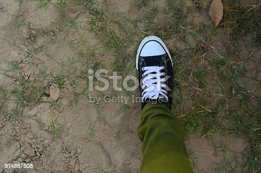 a leg of adult man wear green trouser with black and white shoe stepped on soil ground