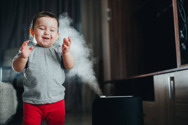 赤いズボンの小さな女の子が見て、加湿器に触れます。家の中の湿気の概念 - 加湿器 ストックフォトと画像