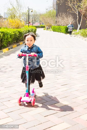 665192886 istock photo a little girl playing skate scooter 1145134103