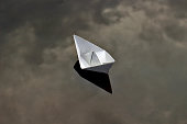 a lone paper boat in the water, reflecting the clouds