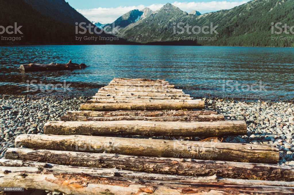 a long pier leading out onto the lake, sunrise on lake, long way out stock photo
