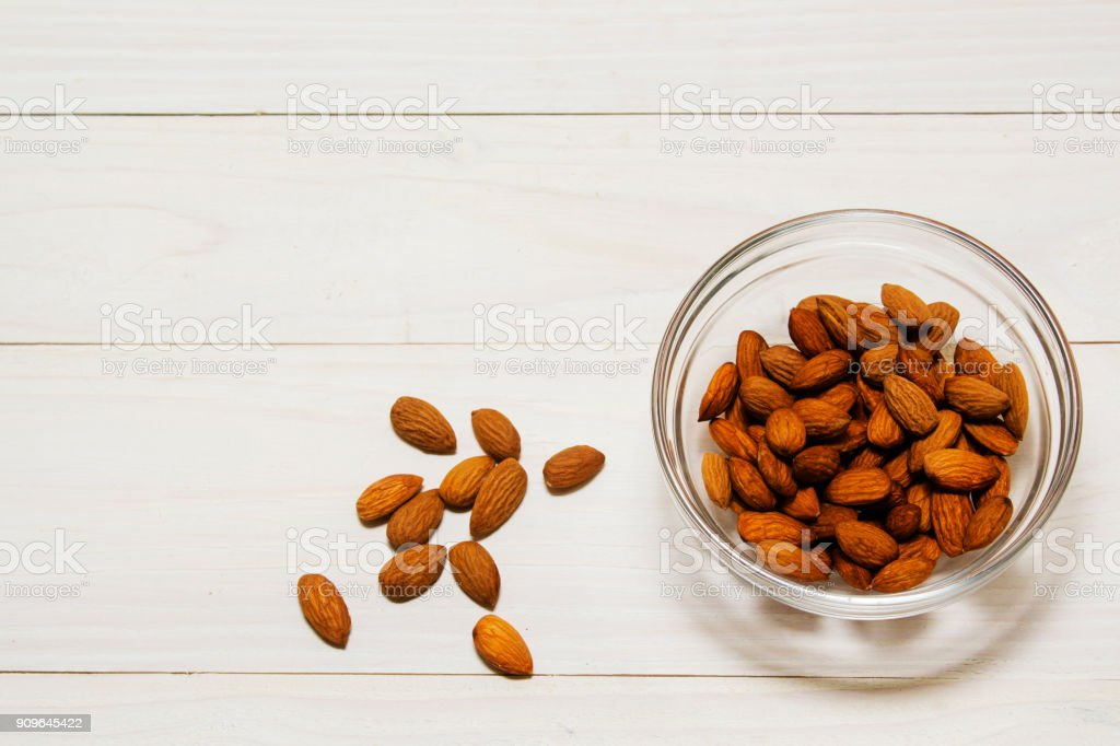a lot of almonds in glass containers, on a light wooden background. stock photo