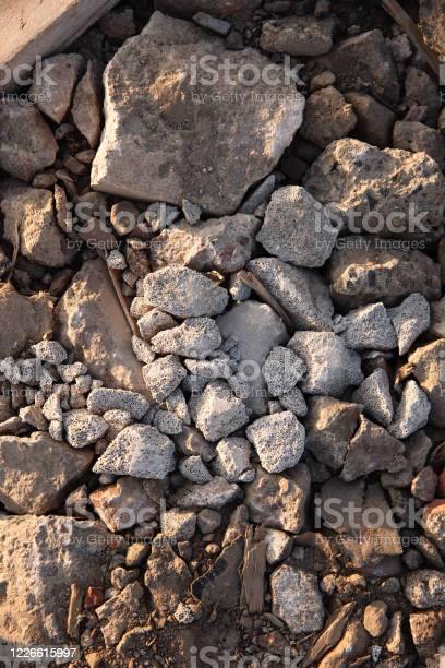 Photo of a lot of kamenets lies on the ground, brown texture, sand and debris in the mix