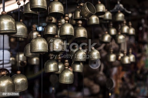 istock a lot of small  brass brass bells hanging in the small souvenir shop in the asia 691843566