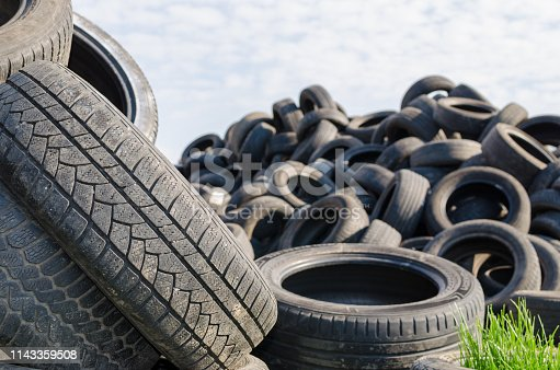 a lot of used tyres with green grass in one of against blue sky with white clouds.