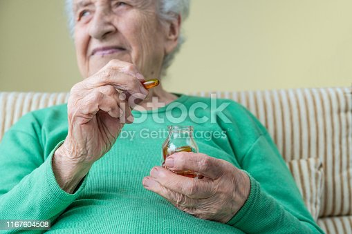 a lovely senior woman holding vitamin capsule and its jar