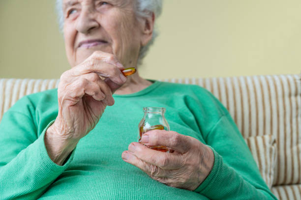 una mujer encantadora de la tercera edad sosteniendo cápsulas de vitaminas - omega 3 fotografías e imágenes de stock