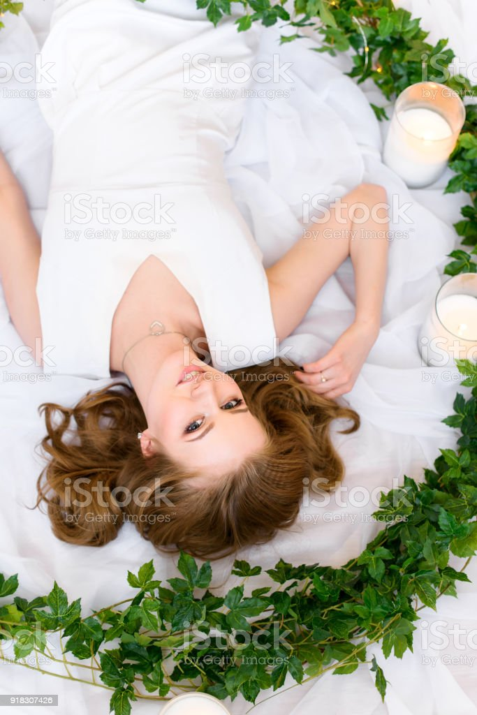 a lovely young lady lying upside down the picture touching her hair gently looking amicably into the camera and smiling charmingly stock photo