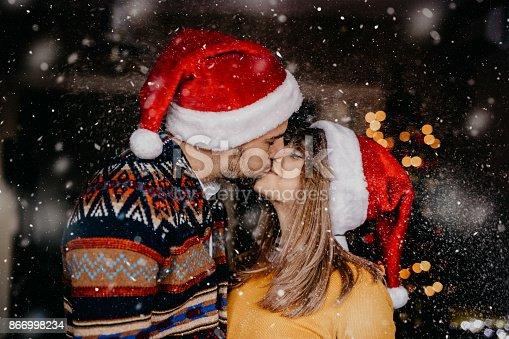 a loving couple kissing outside while snow falls