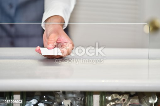 Close up of a male hand holding a credit card through a safety partition on an out of focus background. Work and safety concept.