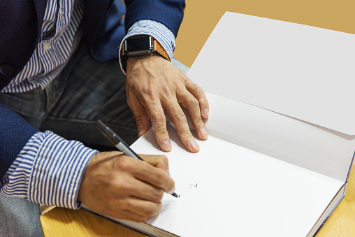 a male writer signing a book