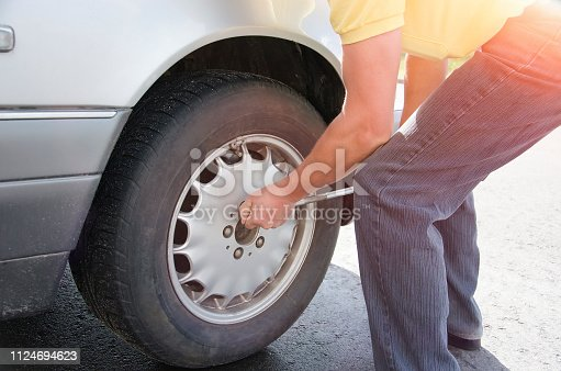 a man changes a wheel on a car outdoors in the rays of backlight