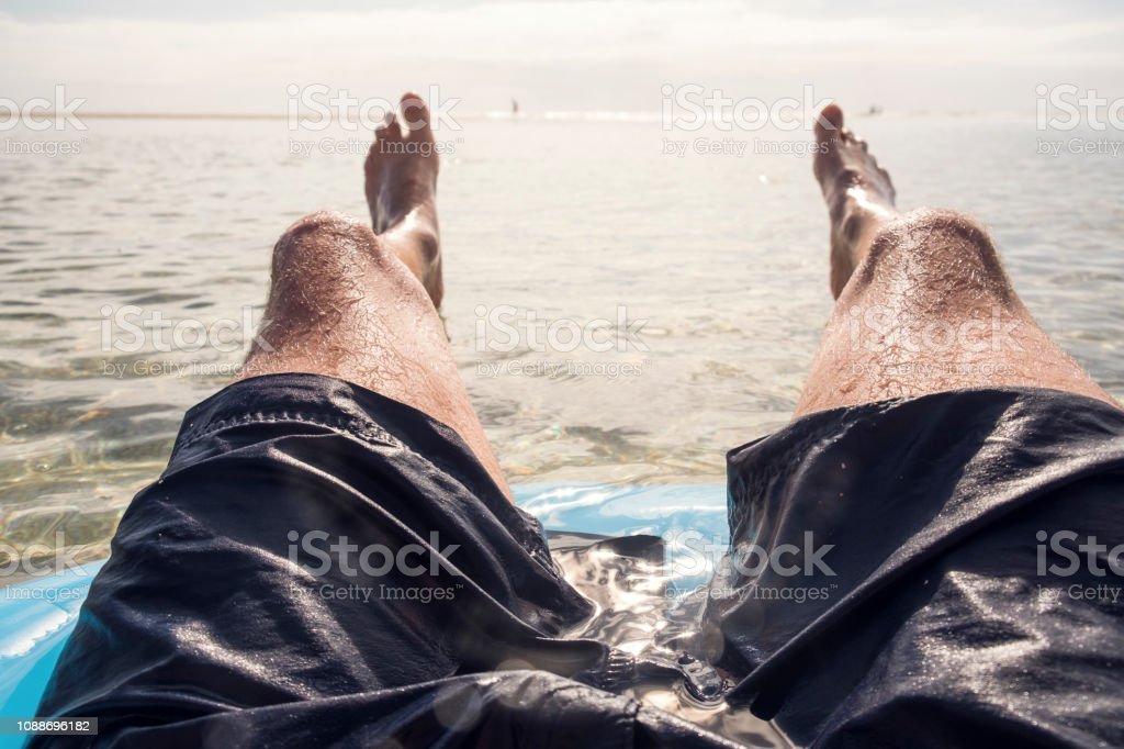 POV of a Man floating in a rubber ring in the sea at Pedn Vounder Beach, South Cornwall on a bright sunny day. stock photo