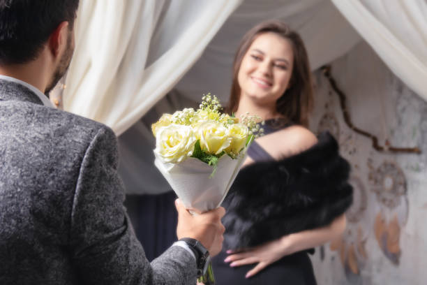 a man gives a bouquet of yellow roses to his beloved woman . focus on colors. the girl is blurry a man gives a bouquet of yellow roses to his beloved woman . focus on colors. the girl is blurry sentimentality stock pictures, royalty-free photos & images